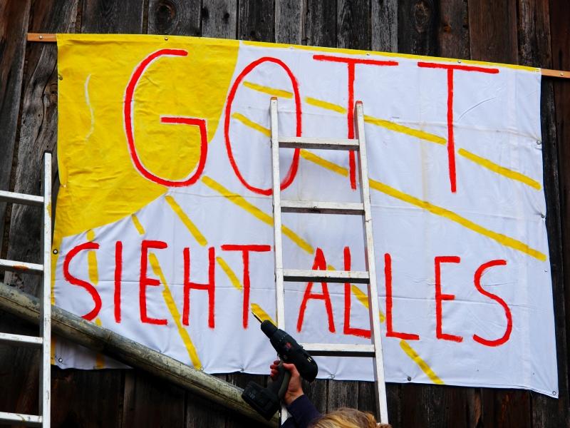 """""""Gott sieht alles""""! Aufhängung des ersten Transparentes einer 16 Meter langen Aufklärungsfront zur Anprangerung und Aufdeckung von Sexuellem Missbrauch von Frauen an eigenen und ihnen anvertrauten Kindern."""