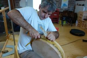 Abschneiden der überstehenden Felle vor Anbringen der Zierbänder. Ron Palesch. Trommler und Trommelbauer.